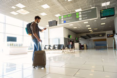 Male tourist waiting for flight. I am in time. Confident young man is looking at watch at airport with concentration. He is standing and carrying suitcase with Royalty Free Stock Image