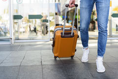 Male tourist walking with luggage. Close up of legs of young man going into the airport with suitcase Royalty Free Stock Photos