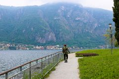 Male tourist walking near banister, lake Como and Alps mountain in background. Male tourist wearing camouflage jacket and walking near banister, lake Como and Stock Image