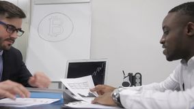 Male traider is giving a paper report on bitcoin market situation to his african boss. Businessmen ae sitting at the table in boardroom and discussing the stock video footage