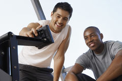 Male Trainer Adjusting Exercising Machine For Man Stock Photos
