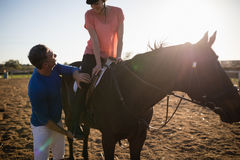 Male trainer adjusting young woman leg on stirrup. Male trainer adjusting young women leg on stirrup at barn Stock Photos
