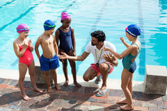 Male trainer assisting children at poolside. High angle view of male trainer assisting children at poolside Stock Image