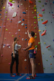 Male trainer assisting female athlete in climbing wall at gym Stock Photos