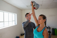 Male trainer assisting female athlete in lifting kettlebells. At gym Royalty Free Stock Photo