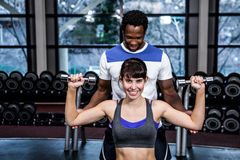 Male trainer assisting fit woman. Male trainer assisting fit women at gym Stock Photos