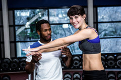 Male trainer assisting fit woman. Male trainer assisting fit women at gym Stock Images