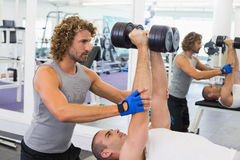 Male trainer assisting man with dumbbells in gym. Side view of a male trainer assisting young men with dumbbells in the gym Royalty Free Stock Photo