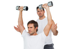 Male trainer assisting man with dumbbells. Male trainer assisting young men with dumbbells over white background Stock Photography