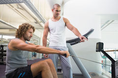 Male trainer assisting man on fitness machine at gym Stock Photos