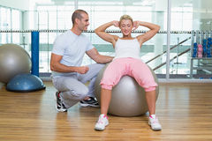Male trainer assisting woman with abdominal crunches at gym. Full length of a male trainer assisting women with abdominal crunches at the gym Stock Photos