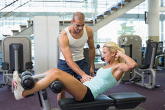 Male trainer assisting woman with abdominal crunches at gym. Side view of a male trainer assisting women with abdominal crunches at the gym Royalty Free Stock Photography