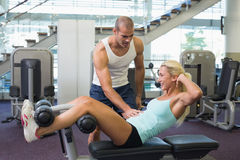 Male trainer assisting woman with abdominal crunches at gym. Side view of a male trainer assisting women with abdominal crunches at the gym Stock Photos