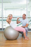 Male trainer assisting woman with abdominal crunches at gym. Side view of a male trainer assisting women with abdominal crunches at the gym Stock Image