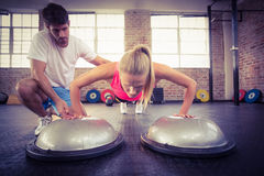 Male trainer assisting woman doing push ups Royalty Free Stock Image