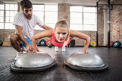 Male trainer assisting woman doing push ups. Male trainer assisting women doing push ups in crossfit gym Royalty Free Stock Photography