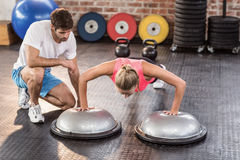 Male trainer assisting woman doing push ups. Male trainer assisting women doing push ups in crossfit gym Royalty Free Stock Photos