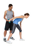 Male trainer assisting woman with dumbbell Royalty Free Stock Images
