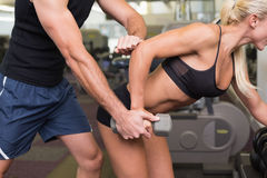 Male trainer assisting woman with dumbbell in gym. Side view of a male trainer assisting women with dumbbell in the gym Stock Photography