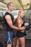 Male trainer assisting woman with dumbbell in gym. Side view of a male trainer assisting women with dumbbell in the gym Stock Images