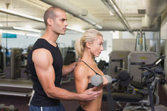 Male trainer assisting woman with dumbbell in gym. Side view of a male trainer assisting women with dumbbell in the gym Stock Photo