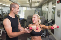 Male trainer assisting woman with dumbbell in gym. Smiling male trainer assisting women with dumbbell in the gym Royalty Free Stock Images