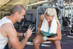 Male trainer assisting woman with dumbbell in gym. Smiling male trainer assisting women with dumbbell in the gym Stock Image