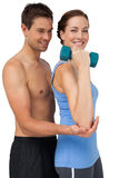 Male trainer assisting woman with dumbbell. Side view of a male trainer assisting women with dumbbell over white background Stock Images
