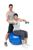 Male trainer assisting woman with dumbbells. Portrait of a male trainer assisting women with dumbbells over white background Stock Photography