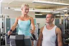 Male trainer assisting woman with exercise bike at gym Royalty Free Stock Photography