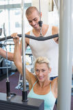 Male trainer assisting woman on lat machine in gym. Male trainer assisting beautiful young women on a lat machine in gym Royalty Free Stock Photos