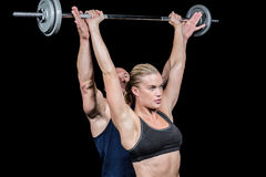 Male trainer assisting woman for lifting crossfit Stock Photos