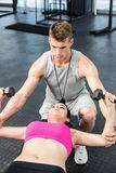 Male trainer assisting woman lifting dumbbell Stock Photos