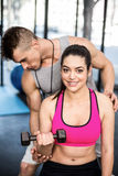 Male trainer assisting woman lifting dumbbell. Male trainer assisting women lifting dumbbell at crossfit gym Royalty Free Stock Photography
