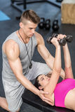 Male trainer assisting woman lifting dumbbells. Male trainer assisting women lifting dumbbells at crossfit gym Royalty Free Stock Photo