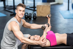 Male trainer assisting woman lifting dumbbells. Male trainer assisting women lifting dumbbells at crossfit gym Royalty Free Stock Image