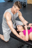 Male trainer assisting woman lifting dumbbells Stock Photos