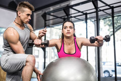 Male trainer assisting woman lifting dumbbells. Male trainer assisting women lifting dumbbells at crossfit gym Stock Photography