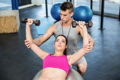 Male trainer assisting woman lifting dumbbells. Male trainer assisting women lifting dumbbells at crossfit gym Royalty Free Stock Images