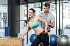 Male trainer assisting woman lifting dumbbells. Male trainer assisting women lifting dumbbells at crossfit gym Royalty Free Stock Photography