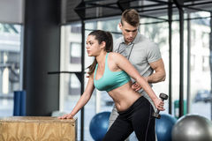 Male trainer assisting woman lifting dumbbells. Male trainer assisting women lifting dumbbells at crossfit gym Stock Images