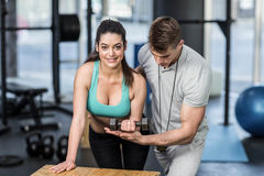 Male trainer assisting woman lifting dumbbells. Male trainer assisting women lifting dumbbells at crossfit gym Stock Photo