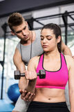 Male trainer assisting woman lifting dumbbells. Male trainer assisting women lifting dumbbell at crossfit gym Royalty Free Stock Image