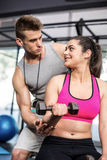 Male trainer assisting woman lifting dumbbells. Male trainer assisting women lifting dumbbell at crossfit gym Royalty Free Stock Photography