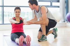 Male trainer assisting woman with pilate exercises in fitness studio Royalty Free Stock Image