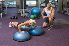 Male trainer assisting woman with push ups at gym. Side view of a male trainer assisting women with push ups at the gym Stock Photo