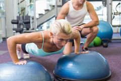 Male trainer assisting woman with push ups at gym. View of a male trainer assisting women with push ups at the gym Royalty Free Stock Image