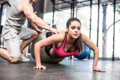Male trainer assisting woman with push ups. Male trainer assisting women with push ups at crossfit gym Stock Photography