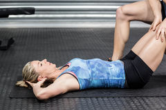 Male trainer assisting woman with sit ups Royalty Free Stock Images