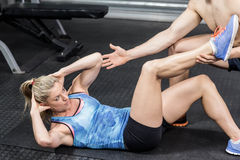 Male trainer assisting woman sit ups Royalty Free Stock Images